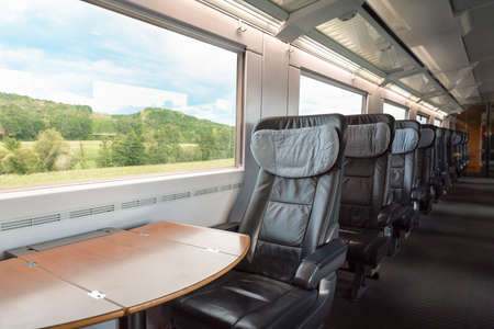 Intercity-Express train interior with empty seats, at business class, in motion. Inside of high-speed German train, at first-class with cozy chairs.