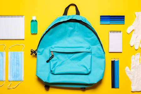 Back to school flat lay with face masks, gloves,  hand sanitizer, and school supplies. Blue backpack, hygiene objects, and school supplies isolated on a yellow background.