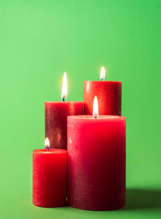 Group of lit candles isolated on a green colored background. Wax candles red-colored. Red candles on a green table. Reklamní fotografie