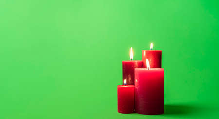 Burning red candles isolated on a green background. Lit candles minimalist on a green colored table. Reklamní fotografie