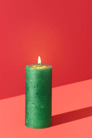 Christmas candle, burning, isolated on a red background. Wax candle green colored. Holiday card with a lit candle and copy space.