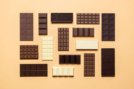 Chocolate bar assortment isolated on a beige background. Top view of fine chocolate collection, dark, milk, and white. Assorted baking chocolate.