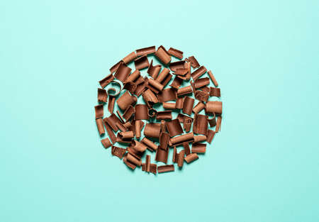 Chocolate shavings, circle shaped layout, isolated on a blue background. Top view of milk chocolate pieces. Decorative ingredients for desserts.