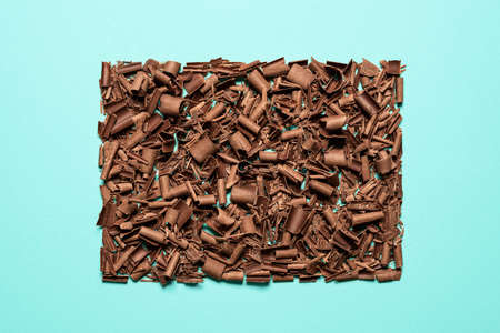 Chocolate pieces and curls isolated on a seamless blue background. Flat lay of grated chocolate symmetrically displayed. Decorative chocolate shavings. Reklamní fotografie