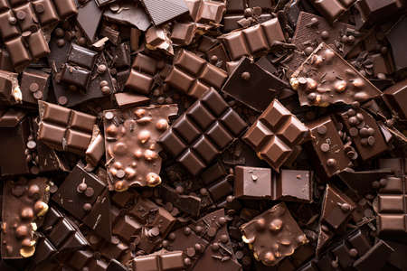 Assorted chocolate bar and chunks, background. Flat lay with a multitude of chocolate kinds. Delicious cocoa dessert. Baking chocolate collection. Reklamní fotografie