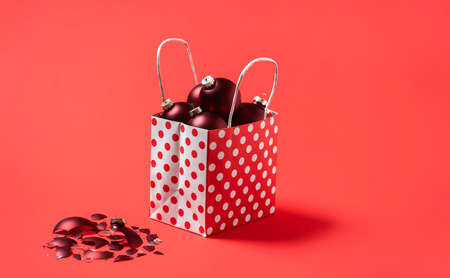 Christmas shopping bag full of red baubles, isolated on a red seamless background. Red Christmas balls in a gift bag. Holiday shopping concept.
