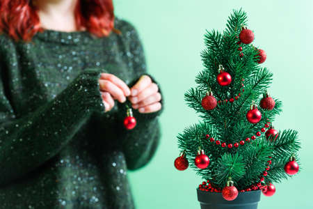 Little Christmas tree in a pot decorated with red Christmas baubles. Young girl in a green and cozy sweater decorating the Christmas tree with small red baubles in the background.