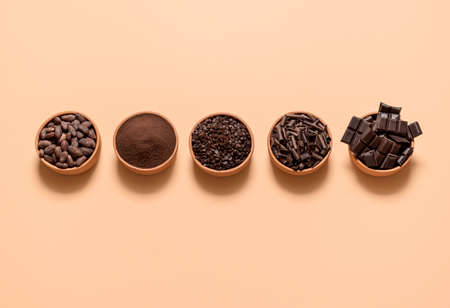 Chocolate ingredients, cacao beans, cocoa powder, chocolate chunks in bowls, isolated on a beige background. Flat lay with cocoa and dark chocolate. Reklamní fotografie