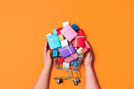 Christmas shopping cart full of colorful gifts, isolated on orange background. Top view with woman buying gifts. Online shopping for Christmas gifts.
