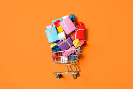Shopping cart with a pile of colorful gifts isolated on orange background. Top view with supermarket cart with presents. Christmas shopping concept.