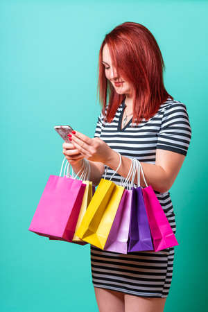 Redheaded young woman holding shopping bags on hands and using the smartphone. Young woman shopping against a cyan-colored background.