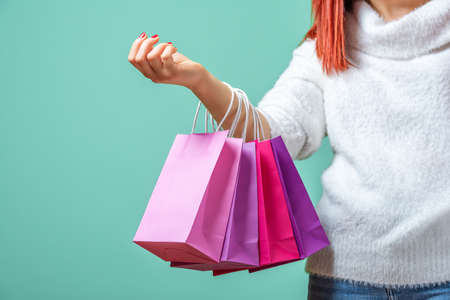 Young redheaded woman holding colored shopping bags on one arm. A woman dressed in a white sweater holding pink and purple paper bags. Reklamní fotografie