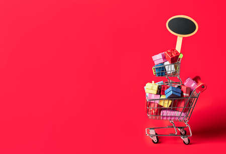 Shopping cart full of colorful gifts and an empty placard, isolated on a red background. Black Friday sale concept. Christmas gift shopping. Reklamní fotografie