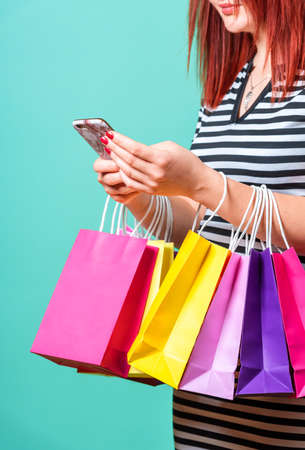 Woman holding shopping bags on her hands and using a smartphone.  Close-up of a redheaded woman shopping with multicolored paper bags.