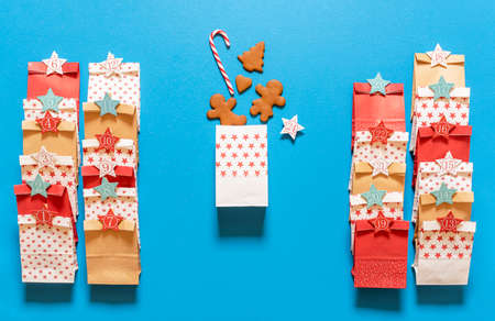 Making advent calendar gift bags with gingerbread cookies and candy canes, on a blue background. Top view with 24 paper bags for Christmas advent.