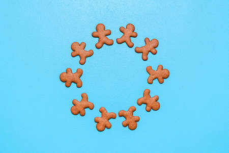 Above view with gingerbread man cookies on a blue background. Cookies arranged in a circle on a table, flat lay Imagens