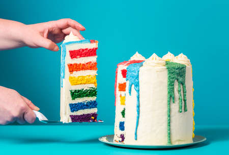 Woman's hands taking a slice of rainbow cake. Delicious homemade birthday cake against a blue background.