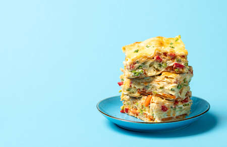 Vegetable lasagna with white sauce, huge portion on plate, on a blue background. Homemade Italian food. Vegetarian dish with peas, carrots and cheese Imagens