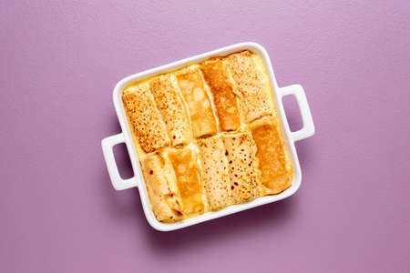 Top view with french pancakes rolls stuffed with curd cheese baked in a tray with sweet cream sauce. Delicious crepes roll filled with cheese.