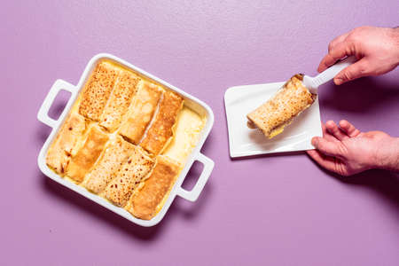 Man hands taking with a spatula stuffed crepes from the tray. French pancakes roll filled with sweet cheese and baked in an oven-tray with cream sauce Imagens