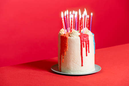 White frosting birthday cake with many candles, isolated on a red background. Homemade buttercream cake for festive events. Celebratory dessert. Imagens