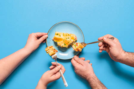People sharing and eating a slice of lasagna, isolated on blue background. Flat lay with vegetable lasagna on a blue plate. Homemade Italian dinner. Imagens