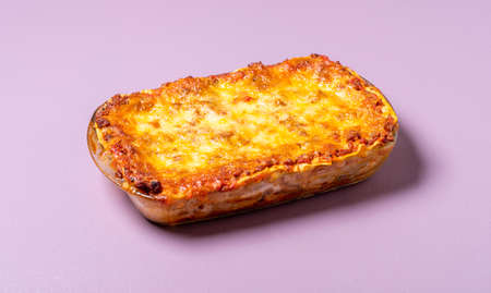 Meat lasagna in tray, freshly-baked, on purple background. Homemade traditional italian lasagna with minced meat, melted mozzarella and tomato sauce.