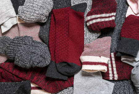 Above view with many multicolored cotton and wool socks. Close-up of a pile with various types of socks.