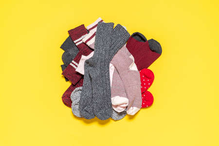 Pile of diverse socks isolated on a yellow-colored background. Top view with socks, various fabrics and colors.