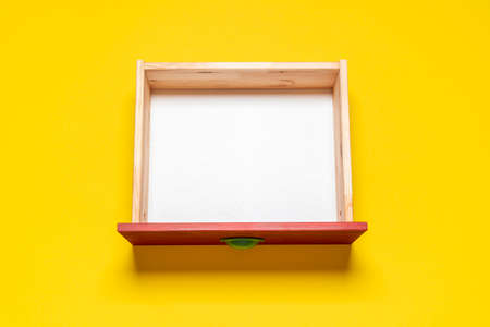Top view with an empty drawer isolated on a yellow background. Wooden drawer with white interior, view from above.