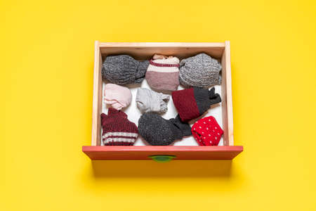 Top view with wooden drawer with socks on a yellow background. Variety of socks in a drawer isolated on colored background.