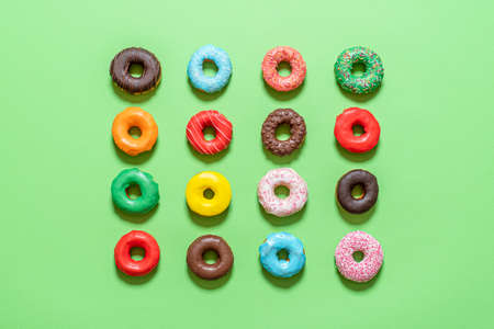 Top view with glazed donuts aligned symmetrically on a green background. Variety of multicolored homemade chocolate donuts. Imagens
