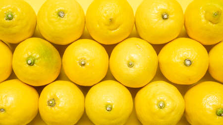 Background with fresh lemons on a yellow background. Full-frame pattern with organic lemons. Imagens