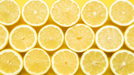 Yellow background with many sliced lemons, top view close-up. Natural yellow color from a bunch of fresh lemons. Imagens