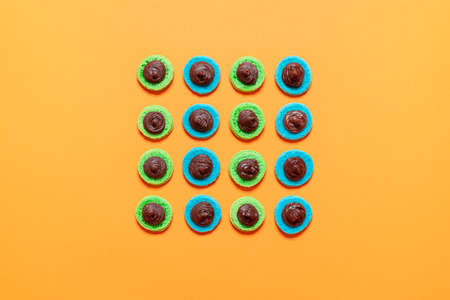 French macaron cookies filled with chocolate ganache, on orange background. Preparation of almond macaroons. Homemade gluten-free meringue cookies. Imagens