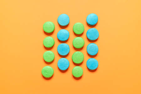 Blue and green macarons symmetrically aligned on an orange background. French macaroons top view. Homemade gluten-free almond meringue cookies. Imagens