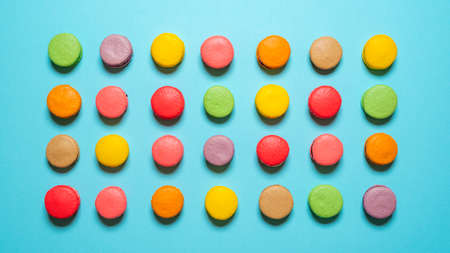 Top view with many homemade macaroons on a blue background. Multicolored macarons isolated on seamless background. Imagens