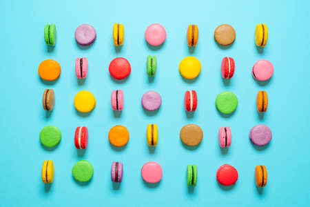 Flat lay with multi-colored homemade macarons isolated on a blue background. Top view with various colors of macarons.