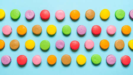 Top view with homemade macarons isolated on a blue background. Multi-colored macarons aligned symmetrically. Sweet macarons baked after the french recipe.
