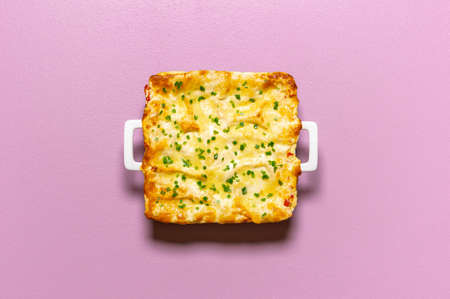 Vegetable lasagna tray with melted cheese, isolated on a purple background. Flat lay with freshly baked vegetarian lasagna. Homemade Italian dinner.