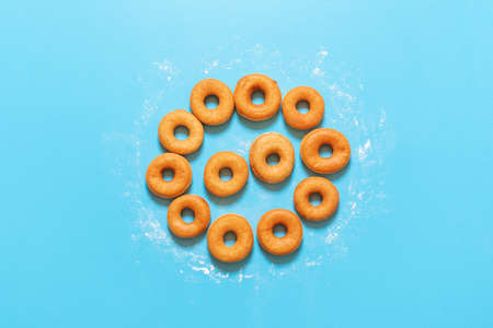 Yeast raised doughnuts aligned in a circle shape, on a blue background. Flat lay with ring donuts on the kitchen table. Homemade fried donuts.