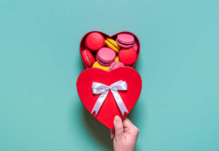 Flat lay with multi-colored macarons arranged in a heart shape on a green background. Delicious homemade macaroons. Imagens