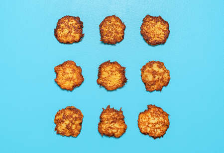 Homemade potato pancakes aligned symmetrically in a square on a blue background. Fried potato pancakes above view.
