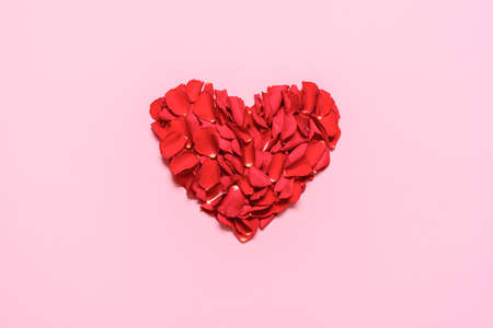 Valentine day heart made of rose petals, isolated on pink background. Flat lay with a romantic red heart. Red roses petals in a heart shaped layout.