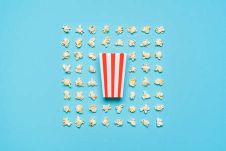 Above view with a striped cardboard box and many pop-corn flakes aligned symmetrically on a blue-colored background. Pop-corn box isolated on a seamless background