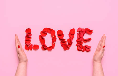 Flat lay with love word from red rose petal letters, on a pink background. Woman hands enfold the word love. A romantic concept for Valentine's day. Imagens