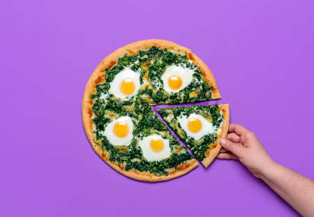 Woman grabbing a slice of pizza. Flat lay, vegetarian pizza with spinach, mozzarella and eggs, isolated on a purple background. Homemade Italian dish Imagens