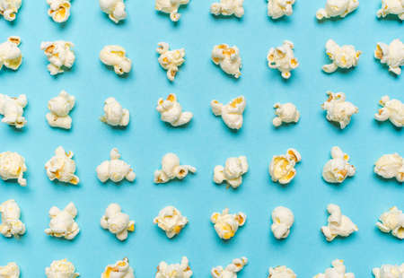 Above view with popcorn flakes arranged symmetrically on a blue background. Full-frame pattern with popped corns.