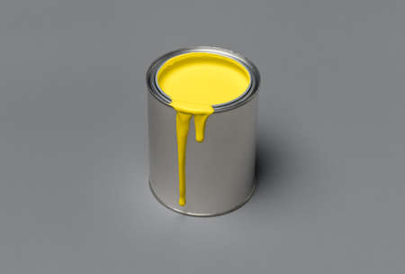 Illuminating yellow paint in a tin can, isolated on ultimate gray background. 2021 colors concept. Can of yellow paint on grey color, minimalist image