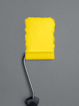 Painting with a paint roller and trendy yellow paint on a gray wall. Flat lay with paint stroke. 2021 color trends concept. Interior design.
